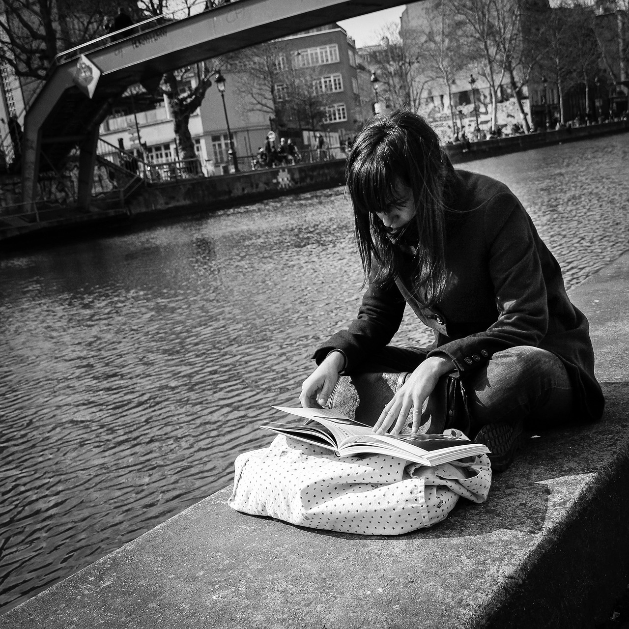 Working in Paris as a Student - girl reading by the canal