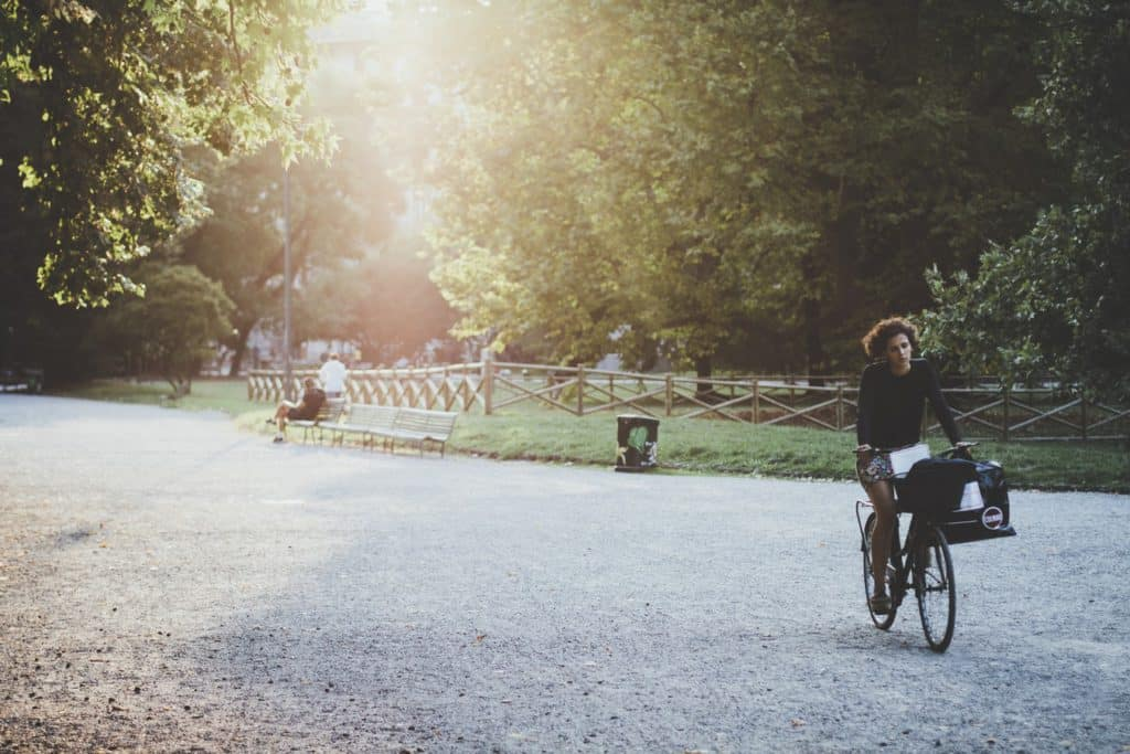 a woman cycling through a park