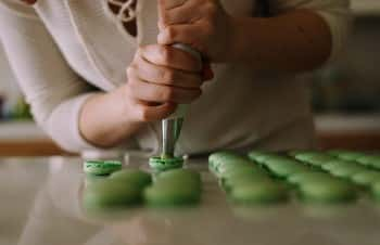 A person piping macarons