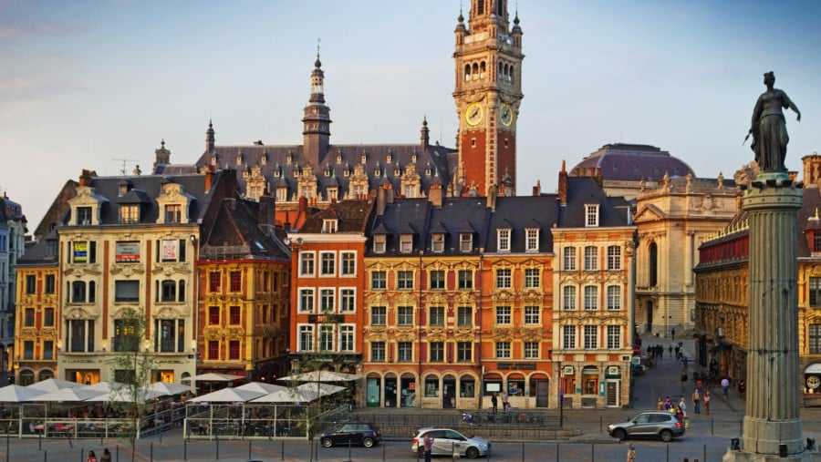 Lille, United Kingdom - August 28, 2013: Panorama of Lille Grand Palais with some tourists in the foreground. There are cobered seating areas outside the restaurants and cars travelling at the bottom of the shot.
